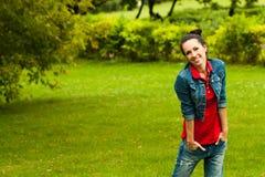 Mujer bonita en los tejanos que se colocan en una hierba Foto de archivo libre de regalías
