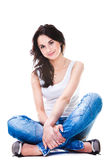 Mujer bonita en los tejanos que se sientan en el suelo blanco Imagen de archivo