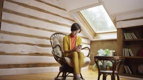 Mujer bonita en los vidrios que mandan un SMS en mensajero en smartphone en ático almacen de metraje de vídeo