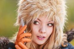 Mujer bonita en sombrero de piel que habla en el teléfono móvil Fotografía de archivo libre de regalías