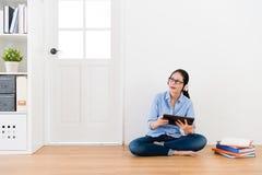 Mujer bonita feliz del estudiante que se sienta en piso de madera Foto de archivo libre de regalías
