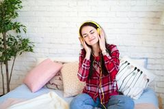 Mujer bonita feliz en auriculares que escucha la música y que canta mientras que se sienta en cama y sostiene el teléfono móvil Fotografía de archivo libre de regalías