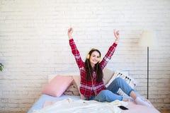 Mujer bonita feliz en auriculares que escucha la música y que canta mientras que se sienta en cama y sostiene el teléfono móvil Fotografía de archivo