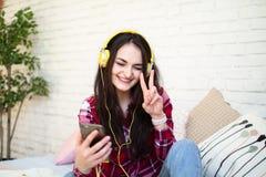 Mujer bonita feliz en auriculares que escucha la música y que canta mientras que se sienta en cama y sostiene el teléfono móvil imagen de archivo