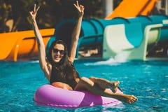 Mujer bonita feliz en el anillo de la nadada en la piscina fotos de archivo