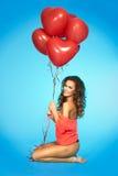 Mujer bonita feliz que celebra el manojo de balones de aire rojos en el estudio Foto de archivo libre de regalías