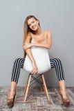 Mujer bonita feliz que se sienta en la silla Imágenes de archivo libres de regalías