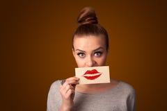 Mujer bonita feliz que sostiene la tarjeta con la marca del lápiz labial del beso Fotos de archivo