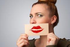 Mujer bonita feliz que sostiene la tarjeta con la marca del lápiz labial del beso Imagenes de archivo
