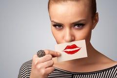 Mujer bonita feliz que sostiene la tarjeta con la marca del lápiz labial del beso Fotografía de archivo