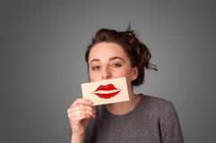 Mujer bonita feliz que sostiene la tarjeta con la marca del lápiz labial del beso Imagen de archivo libre de regalías