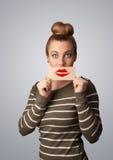 Mujer bonita feliz que sostiene la tarjeta con la marca del lápiz labial del beso Fotos de archivo libres de regalías