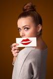 Mujer bonita feliz que sostiene la tarjeta con la marca del lápiz labial del beso Foto de archivo