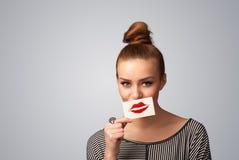 Mujer bonita feliz que sostiene la tarjeta con la marca del lápiz labial del beso Imagen de archivo