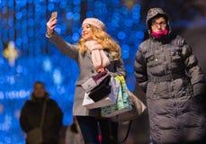 Mujer bonita feliz que toma el selfie en la noche con el decorat de la Navidad Fotografía de archivo
