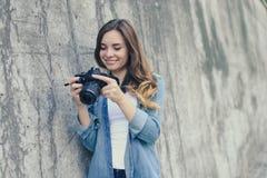 Mujer bonita feliz sonriente que mira imágenes en su cámara digital La visten en ropa casual, pared gris está en el backgr Fotografía de archivo