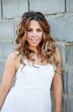 Mujer bonita fresca con una sonrisa hermosa que descansa sobre una pared gris Fotografía de archivo libre de regalías