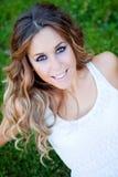 Mujer bonita fresca con una sonrisa hermosa que se sienta en la hierba Fotografía de archivo libre de regalías