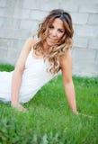 Mujer bonita fresca con una sonrisa hermosa que se sienta en la hierba Fotos de archivo
