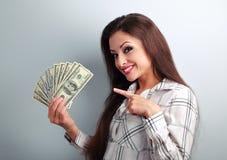 Mujer bonita joven acertada feliz que muestra el finger en dólar Foto de archivo