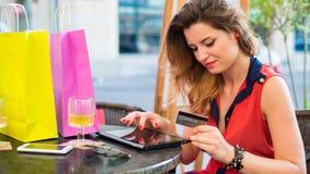 Mujer bonita joven con el cojín que sostiene la tarjeta de crédito. Ella está localizando en café. Foto de archivo