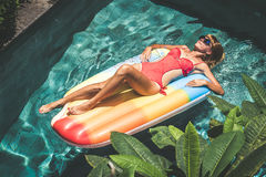 Mujer bonita joven con el cuerpo bronceado perfecto que miente en el colchón de aire en la piscina en verano y que se divierte At Foto de archivo libre de regalías