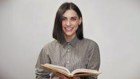 Mujer bonita joven con el pelo marrón corto que lleva a cabo el libro y la lectura, entonces mirando in camera y sonriendo, fondo almacen de video