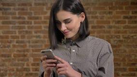 Mujer bonita joven con el pelo marrón corto que manda un SMS en el teléfono, sonriendo, fondo de la pared de ladrillo almacen de video
