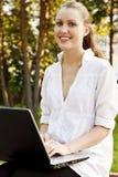 Mujer bonita joven con la computadora portátil Foto de archivo