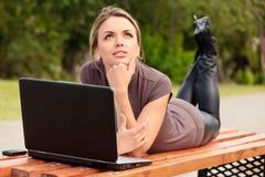 Mujer bonita joven con la computadora portátil que miente en el banco Foto de archivo