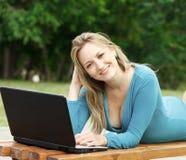 Mujer bonita joven con la computadora portátil Fotografía de archivo libre de regalías