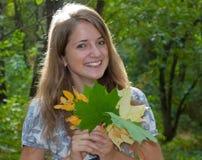 Mujer bonita joven con la hoja del otoño Imagen de archivo libre de regalías