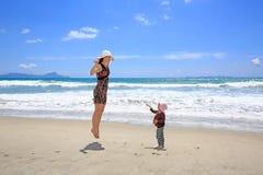 Mujer bonita joven con la pequeña hija que se divierte en Sandy Beach Fotos de archivo