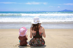 Mujer bonita joven con la pequeña hija que se sienta en Sandy Beach Imágenes de archivo libres de regalías