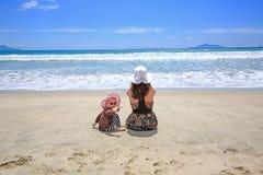Mujer bonita joven con la pequeña hija que se sienta en Sandy Beach Fotos de archivo