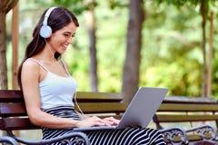 Mujer bonita joven con los auriculares que se sientan en banco en el parque, usando el ordenador portátil Fotos de archivo