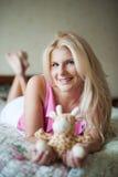 Mujer bonita joven con un juguete en la cama Foto de archivo