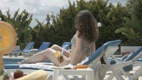 Mujer bonita joven en bikini que camina, teniendo resto en silla de playa metrajes