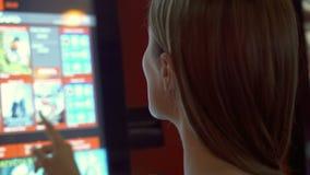 Mujer bonita joven en boleto de compra de la película de la camiseta roja de la máquina expendedora en el cine almacen de video