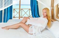 Mujer bonita joven en cama con el océano detrás de la ventana Imagen de archivo