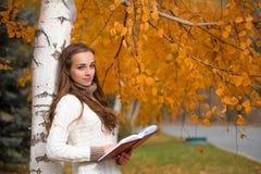Mujer bonita joven en el parque del otoño imagenes de archivo