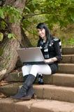 Mujer bonita joven en el parque del otoño con el ordenador Imágenes de archivo libres de regalías