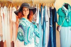 Mujer bonita joven en el sombrero negro que intenta en los nuevos accesorios en tienda de ropa Sonrisa de la mujer y mirada a la  Fotografía de archivo