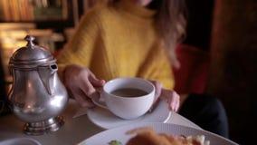 Mujer bonita joven en el suéter amarillo que desayuna en café acogedor y que bebe té metrajes