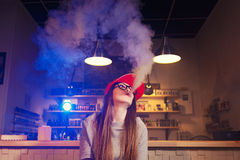 Mujer bonita joven en humo rojo del casquillo un cigarrillo electrónico en la tienda del vape foto de archivo libre de regalías