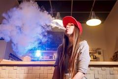 Mujer bonita joven en humo rojo del casquillo un cigarrillo electrónico en la tienda del vape fotografía de archivo