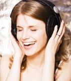 Mujer bonita joven en la música que escucha de los auriculares, cantando a una canción la sonrisa feliz, concepto de la gente de  Imágenes de archivo libres de regalías