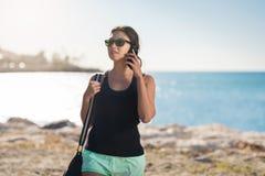 Mujer bonita joven en la playa que habla en móvil Imagen de archivo
