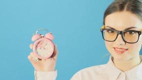 Mujer bonita joven en los vidrios y la camisa que sostienen el reloj rosado en manos en fondo azul brillante en estudio Mida el t almacen de metraje de vídeo