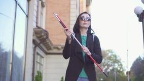 Mujer bonita joven en vidrios con un bastón que camina abajo de la calle almacen de metraje de vídeo